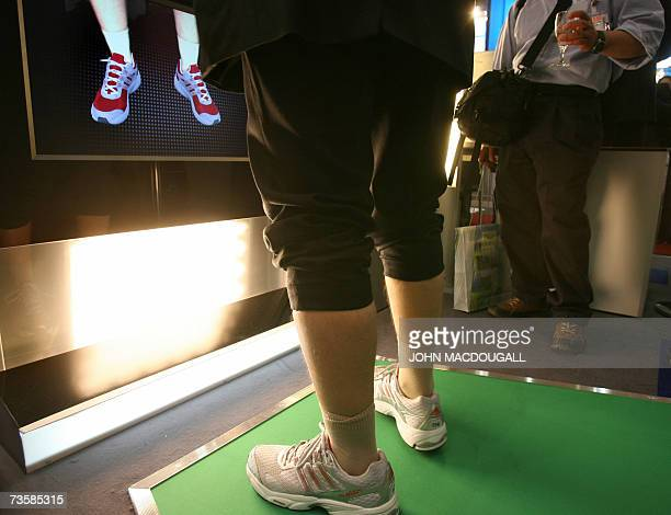 """Worker demonstrates the use of a """"Virtual Mirror for Augmented Reality"""" developed by the Fraunhofer Institute and Adidas at the CeBIT computer,..."""