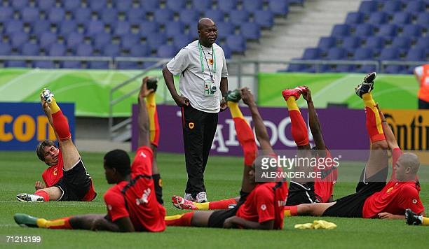 Angolan head coach Luis Goncalves De Oliveira and midfielder Figueiredo are seen with teammates during a training at Hanover stadium 15 June 2006, a...