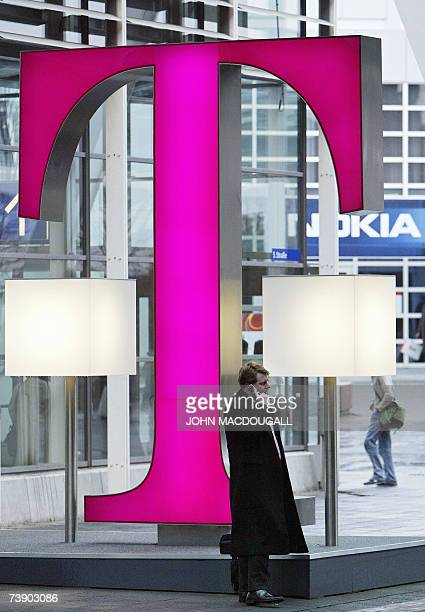FILES A picture taken 11 March 2005 shows a man using his mobile phone as he stands next to the logo of German telecommunications giant Deutsche...