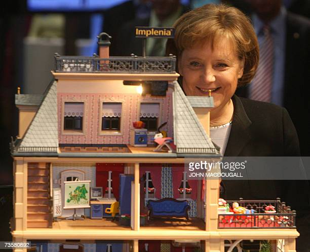 German Chancellor Angela Merkel looks at a model 'intelligent house' at the IBM stand at the CeBIT computer digital IT and telecommunications fair 15...