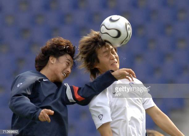 South Korean forward Ahn Jung Hwan and midfielder Lee Ho jump to head the ball during a training session at the World Cup Stadium in Hanover, 22 June...