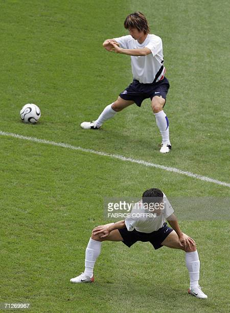 South Korean midfielder Kim Do Heon and forward Chung Kyung-Ho stretch prior to a practice session at the WM-Stadion, 22 June 2006 in Hanover on the...