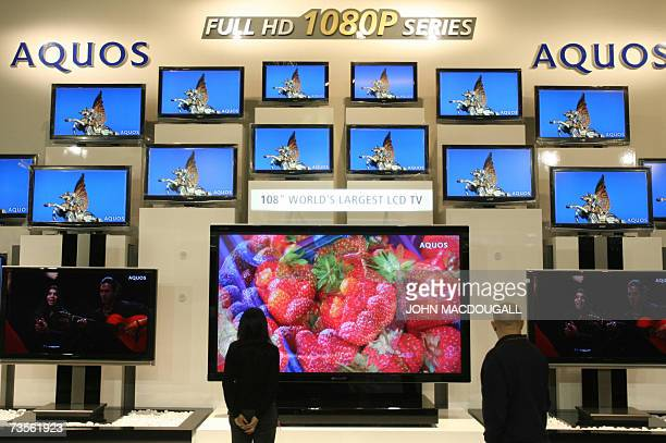 Worker looks at a display of giant LCD TVs by Japanese electronics giant Sharp during preparations for the CeBIT computer digital IT and...