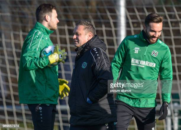 Hanover's coach André Breitenreiter walks across the pitch with his player Kenan Karaman during the first training session of the German Bundesliga...