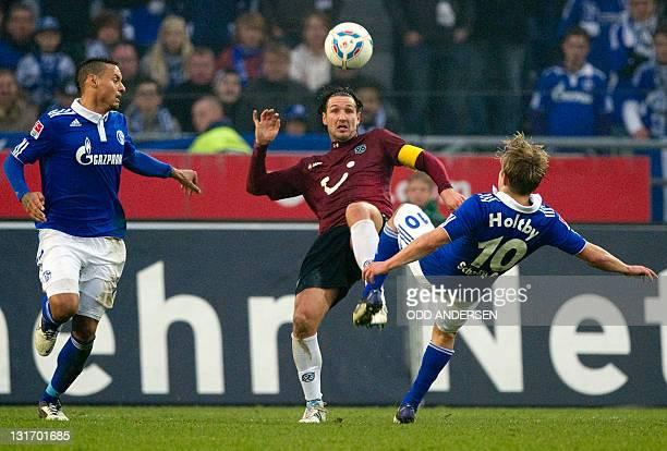 Hanover's defender Christian Schulz Schalke's midfielder Lewis Holtby and Schalke's US midfielder Jermaine Jones vie for the ball during the German...