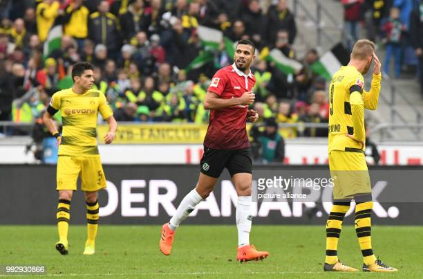Hanover's Jonathas celebrates after giving his side a 10 lead while Dortmund's Marc Bartra and Andrey Yarmolenko look on during the Bundesliga soccer...