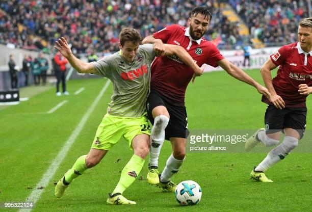 Hanover's Kenan Karaman and Matthias Ostrzolek play against Cologne's Lukas Kluenter vie for the ball during the German Bundesliga match between...