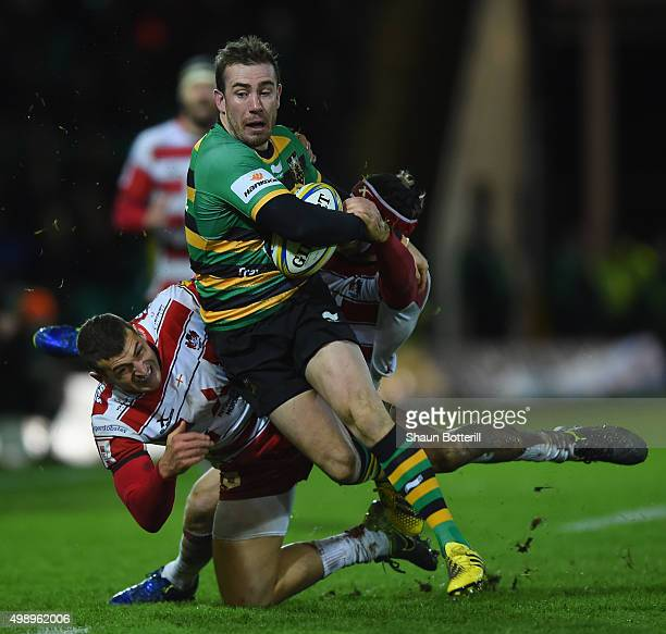 Hanrahan of Northampton Saints is tackled by Jonny May and Rob Cook of Gloucester Rugby during the Aviva Premiership match between Northampton Saints...