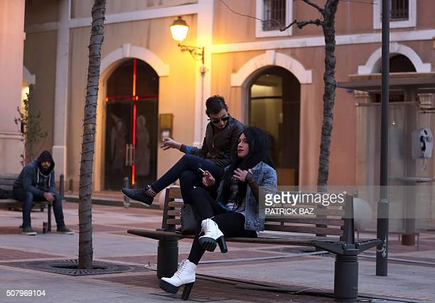 Hans a 22yearold Lebanese drag queen and her transgender friend Toy sit and smoke on a bench in downtown Beirut on February 1 2016 Hans works as a...