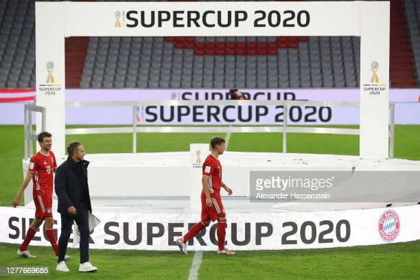 Hans Dieter Flick head coach of FC Bayern Muenchen looks on with his players Thomas Müller and Joshua Kimmich after the Supercup 2020 match between...
