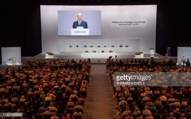 Hans Dieter Poetsch CEO of Porsche Automobil Holding SE is displayed on a screen as he adresses the shareholders during the company's annual...