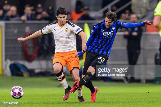 Hans Hateboer of Atalanta attempts a kick while being defended by Carlos Soler of Valencia CF during the UEFA Champions League round of 16 first leg...