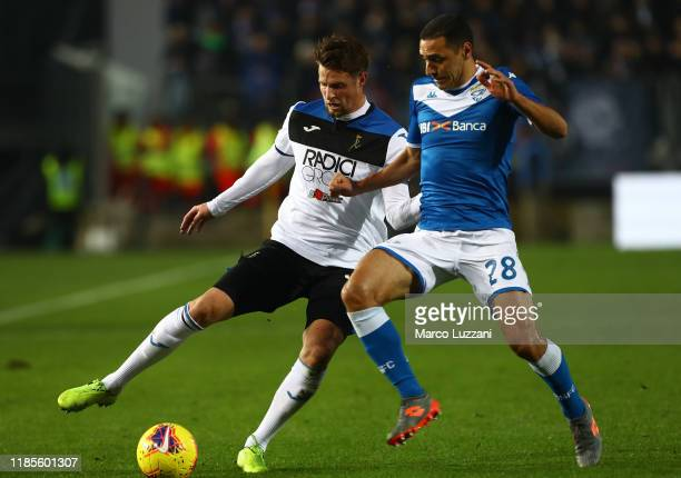 Hans Hateboer of Atalanta BC is challenged by Romulo of Brescia Calcio during the Serie A match between Brescia Calcio and Atalanta BC at Stadio...