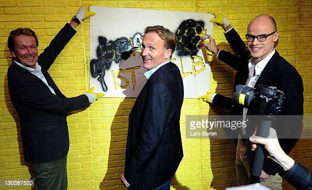 Hans Joachim Watzke, CEO of Borussia Dortmund, sprays on a wall between Matthias Baeumer, director Puma Germany, and Franz Koch, CEO of Puma, during...