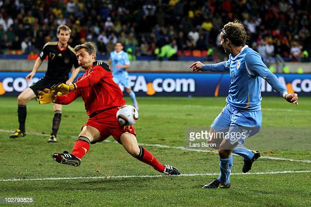 Hans Joerg Butt of Germany blocks the shot of Diego Forlan of Uruguay during the 2010 FIFA World Cup South Africa Third Place Playoff match between...