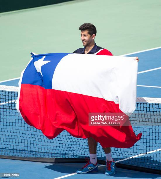 Hans Podlipnik of Chile celebrates with a Chilean national flag during the Davis Cup first round double tennis match against the Dominican Republic...