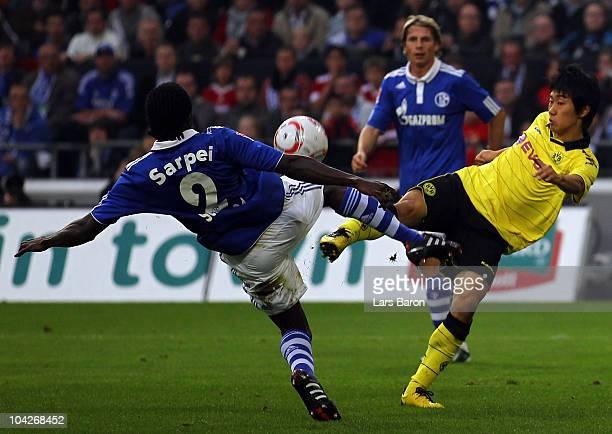 Hans Sarpei of Schalke challenges Shinji Kagawa of Dortmund during the Bundesliga match between FC Schalke 04 and Borussia Dortmund at Veltins Arena...
