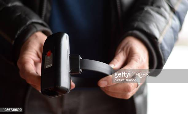 HansDieter Amthor of the IT department of the Hessian department of justice holds up an electronic ankle monitor in Bad Vilbel Germany 11 January...