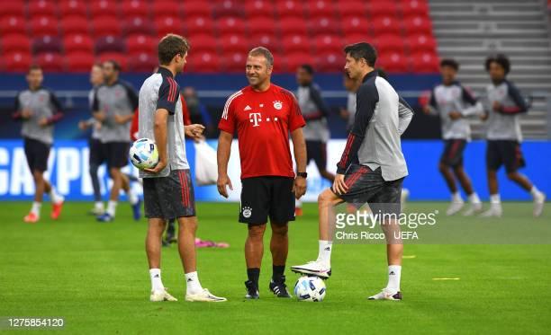 HansDieter Flick Head Coach of Bayern Munich speaks to Thomas Mueller and Robert Lewandowski of Bayern Munich during the Bayern Munich Training...