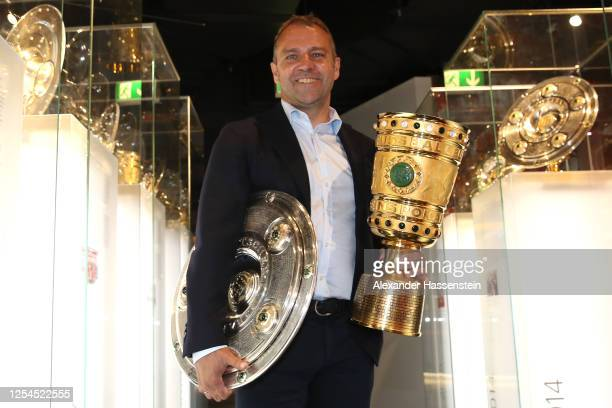 Hans-Dieter Flick, head coach of FC Bayern Muenchen hands over the DFL Championship 2020 winners trophy and DFB Cup 2020 winners trophy to the FCB...