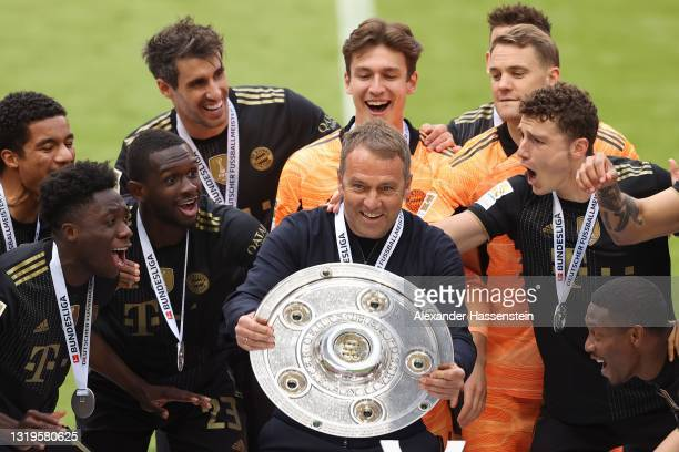 Hans-Dieter Flick, Head coach of FC Bayern Muenchen lifts the Bundesliga Meisterschale Trophy in celebration with his players following the...