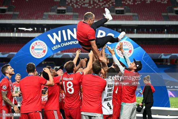 Hans-Dieter Flick, Head Coach of FC Bayern Munich is thrown into the air by his players following their team's victory in the UEFA Champions League...