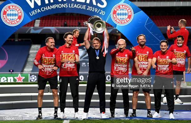 Hans-Dieter Flick, Head Coach of FC Bayern Munich lifts the UEFA Champions League Trophy with his backroom staff following their team's victory in...