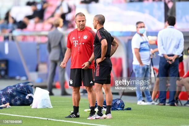 Hans-Dieter Flick, Head Coach of FC Bayern Munich speaks with Thiago Alcantara of FC Bayern Munich during a training session ahead of their UEFA...