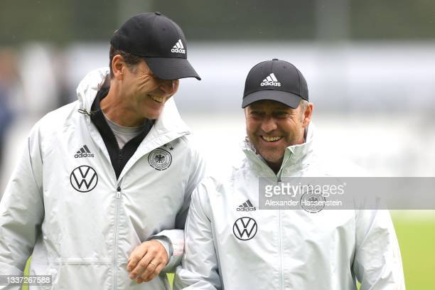 Hans-Dieter Flick, Head Coach of Germany talks to Oliver Bierhoff DFB director for national teams and the DFB academy during a training session at...