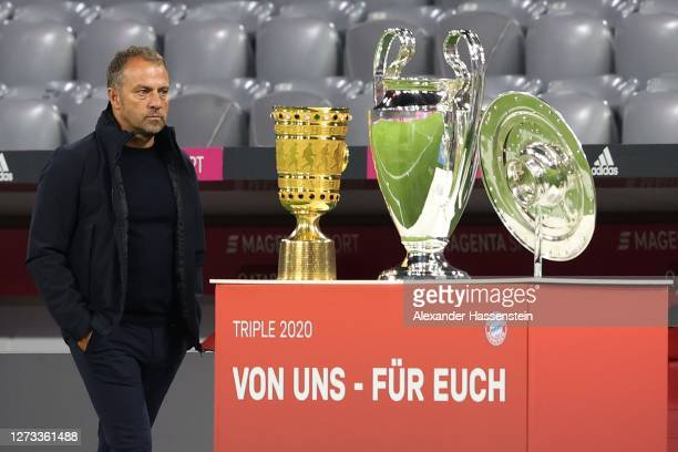 Hans-Dieter Flick, head coach of Munich walks next to the German Cup winners trophy, the Championsleague winners trophy and the German Championship...