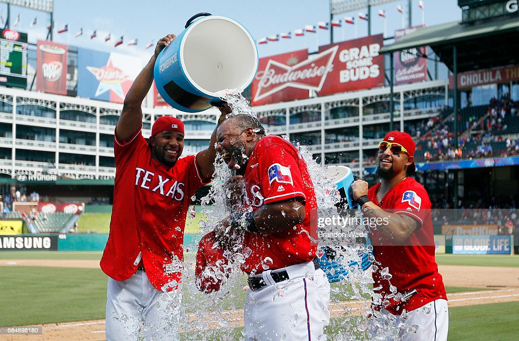 Hanser Alberto #2 of the Texas Rangers, center, reacts to a sports drink shower from Elvis Andrus, left, and Rougned Odor in celebration of a 5-3 win over the Kansas City Royals in a baseball game at Globe Life Park on Sunday, July 31, 2016 in Arlington, Texas.