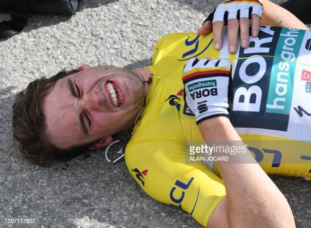 Hansgrohe German rider Maximilian Schachmann overall leader yellow jersey and winner of the Paris - Nice race, lies on the ground exhausted at the...