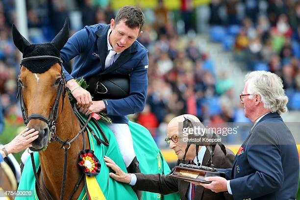 HansGuenter Winkler olympic champions hands out the Hallascha price to Scott Brash of GreatBritain rides on Hello Sanctosh and is accompanied by...
