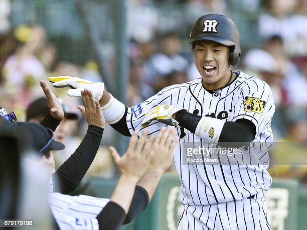 Hanshin Tigers catcher Ryutaro Umeno is welcomed back to the dugout by teammates after crossing the plate in the seventh inning of a Central League...