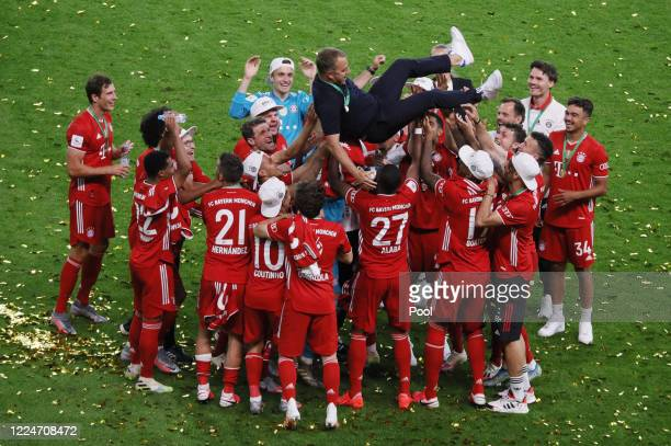 Hansi Flick Manager of Bayern Munich is lifted in the air by his players during the DFB Cup final match between Bayer 04 Leverkusen and FC Bayern...