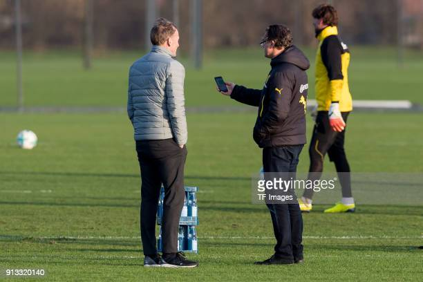 HansJoachim Watzke of Dortmund speaks with Sporting director Michael Zorc of Dortmund during a training session at BVB trainings center on January 30...