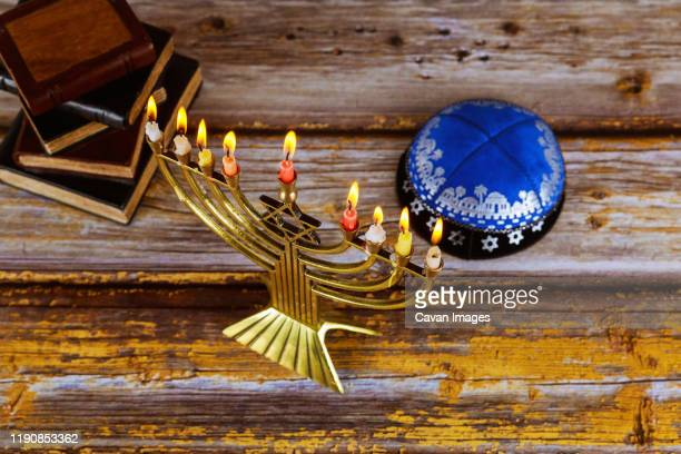hanukkah celebration with menorah with wooden dreidels and candles - hannukkah stock pictures, royalty-free photos & images