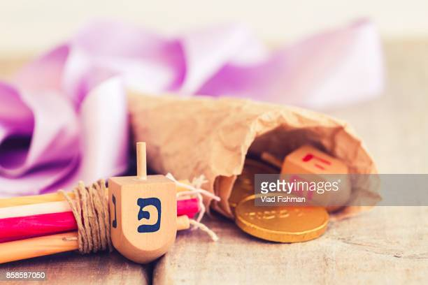 hanukkah dreidels with some hanukkah candles and hanukkah coins on a vintage wood background with copy space. perfect for your hanukkah holiday design - hanukkah imagens e fotografias de stock