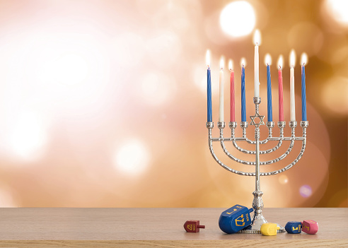 Hanukkah Jewish holiday background with menorah (Judaism candelabra)  burning candles and traditional Dreidrel game toy on wood table and on autumn bokeh sun flare 1034620002