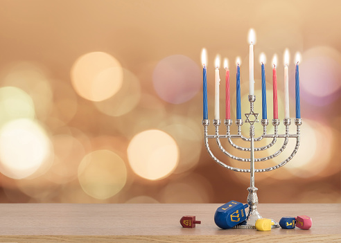 Hanukkah Jewish holiday background with menorah (Judaism candelabra)  burning candles and traditional Dreidrel game toy on wood table and on autumn bokeh sun flare 1061500162