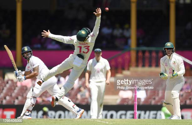 Hanuma Vihari of India gets the ball past a diving Matthew Wade of Australia during day three of the third Test match between Australia and India at...