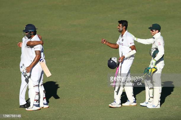 Hanuma Vihari, Ravichandran Ashwin of India and Tim Paine of Australia leave the field after the drawn match during day five of the 3rd Test match in...