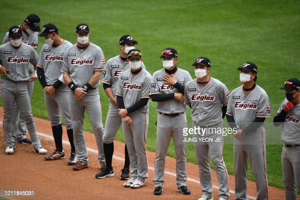 Hanwha Eagles players wearing face masks line up before the start for a ceremony for the opening game of South Korea's new baseball season between...