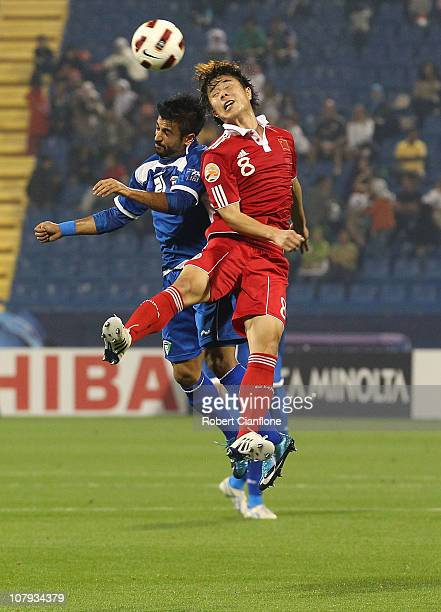 Hao Junmin of China and Abdulaziz Mashan of Kuwait challenge eachother for the ball during the AFC Asian Cup Group A match between China PR and...