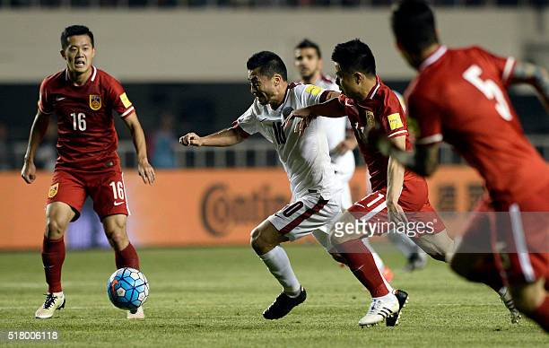Hao Junmin of China competes for the ball with Rodrigo Tabata of Qatar during their 2018 World Cup football qualifying match in Xi'an northwest...