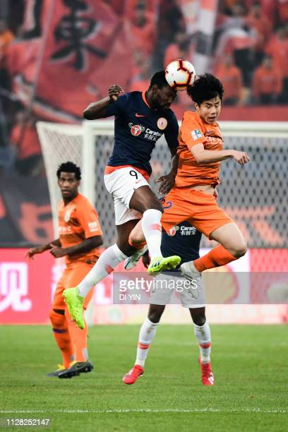 Hao Junmin of Shandong Luneng compete for a header with Diop of Beijing Renhe during the 2019 Chinese Super League match between Shandong Luneng and...