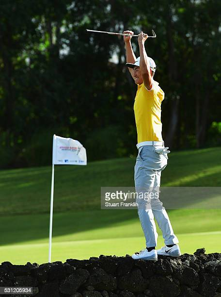 Hao Tong Li of China jumps onto the wall to celebrate after chipping in on the 14th hole during the second round of AfrAsia Bank Mauritius Open at...