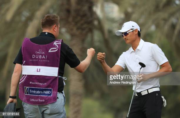 Haotong Li of China celebrates a birdie with his caddie on the 17th green during the final round on day four of the Omega Dubai Desert Classic at...