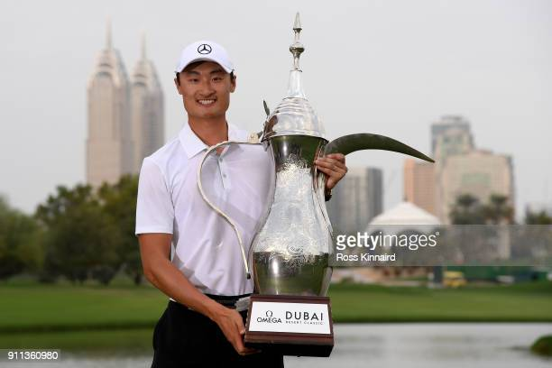 Haotong Li of China celebrates victory with the trophy after the final round on day four of the Omega Dubai Desert Classic at Emirates Golf Club on...