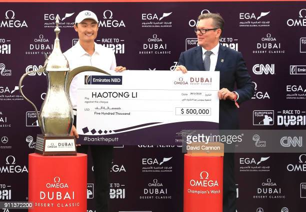 Haotong Li of China is presented with the winner's cheque by Shane Nelson the CEO of Emirates NBD after the final round of the Omega Dubai Desert...